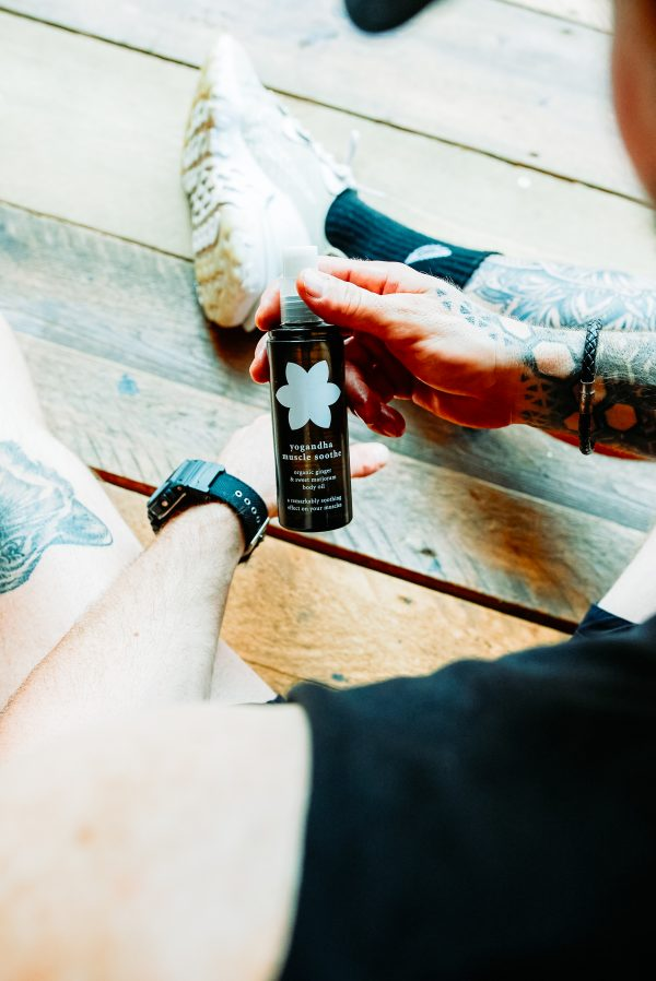 Muscle Soothe Body Oil - 3. Lifestyle shot fitness guy holding Yogandha Muscle S